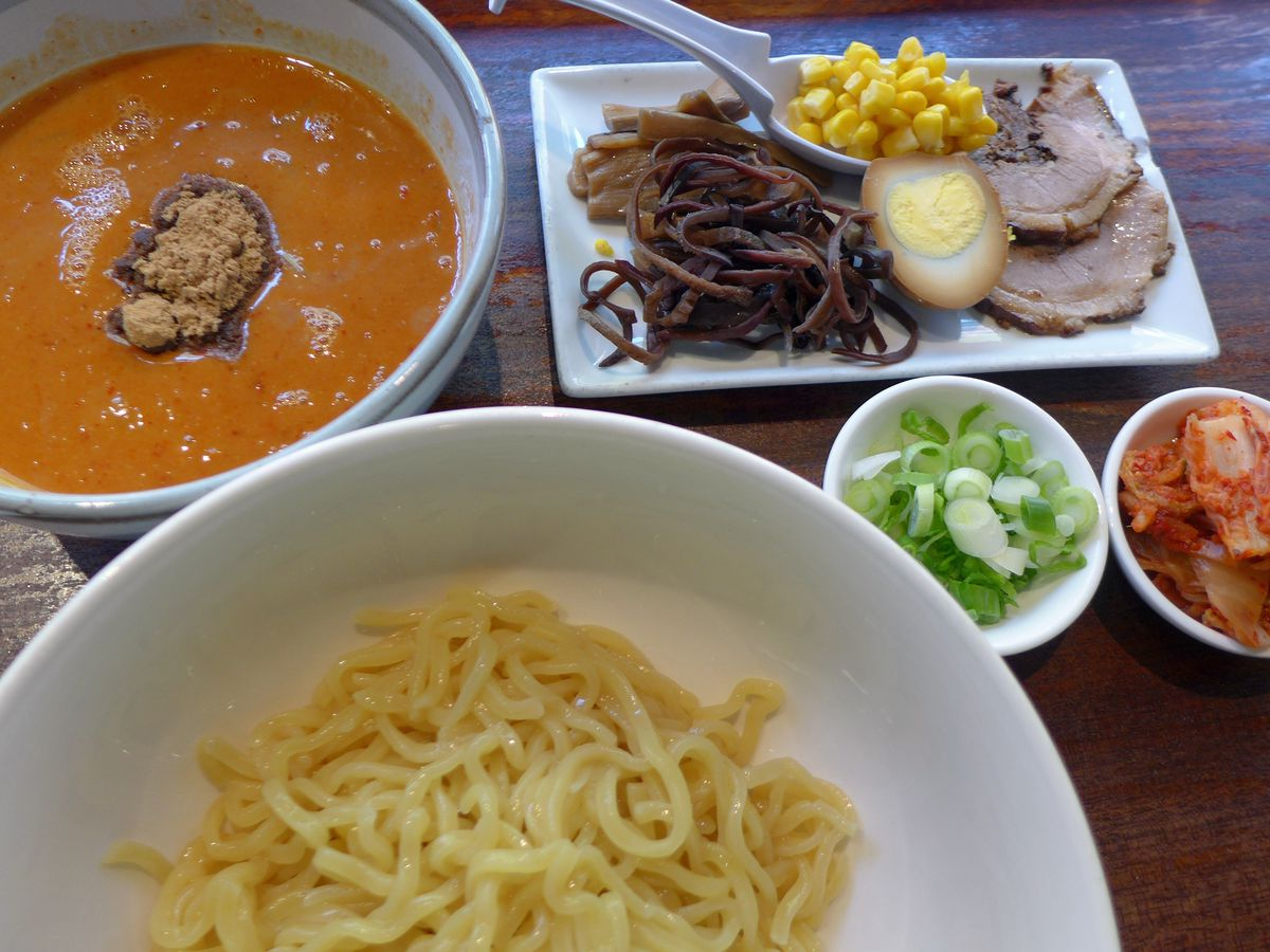 A deconstructed bowl of noodles in the tsukemen style, with a fiery broth and several add ins on the side.