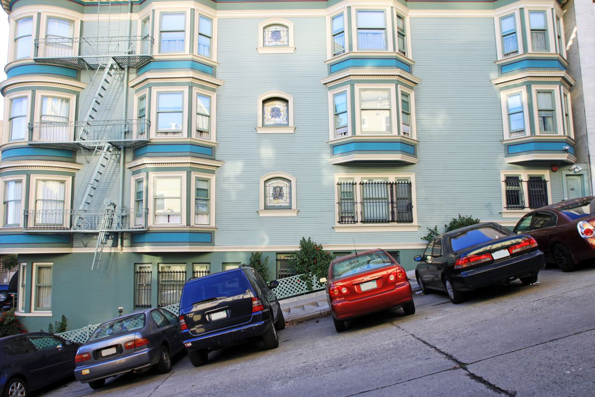 A view of a typical San Francisco bay windows on a hill with parked cars.