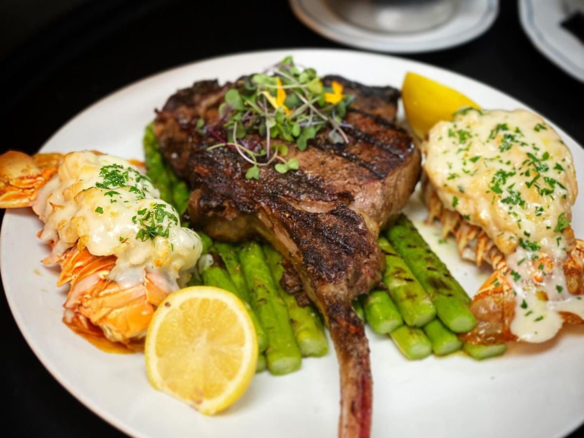Surf and turf features a 32-ounce tomahawk ribeye and two 9-ounce lobster tails