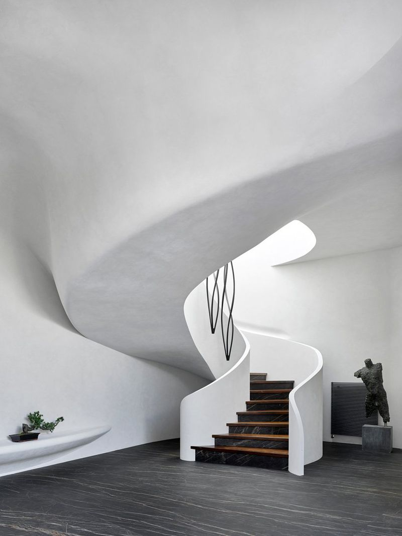 Curving white staircase and brown floors.