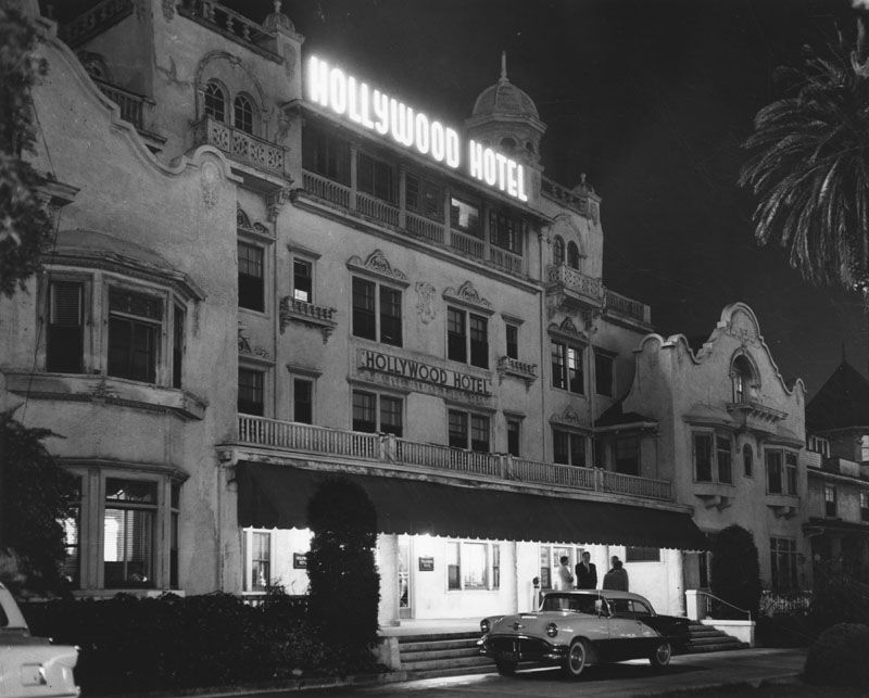 The exterior of the Hollywood Hotel. The building has multiple floors. There is a car in front of the hotel.