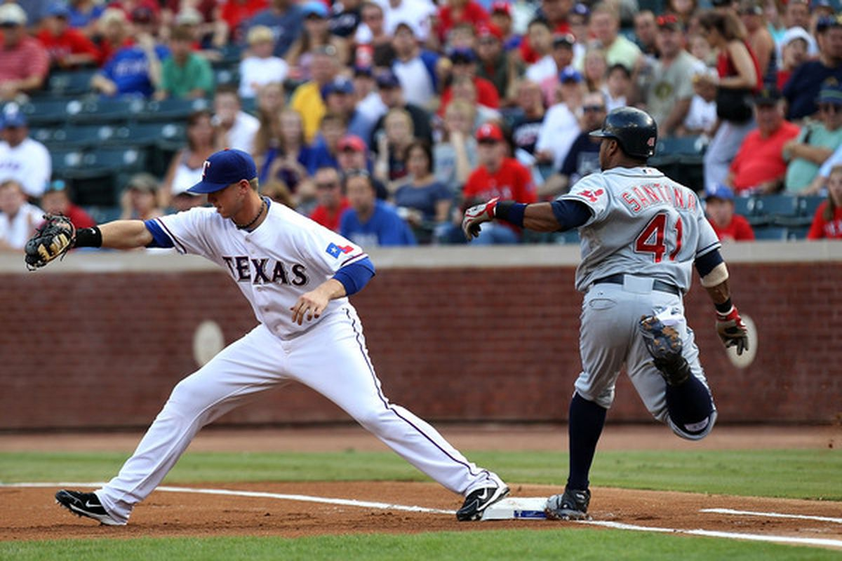 ARLINGTON TX - JULY 07:  First baseman Justin Smoak #12 of the Texas Rangers makes the out against Carlos Santana #41 of the Cleveland Indians on July 7 2010 at Rangers Ballpark in Arlington Texas.  (Photo by Ronald Martinez/Getty Images)