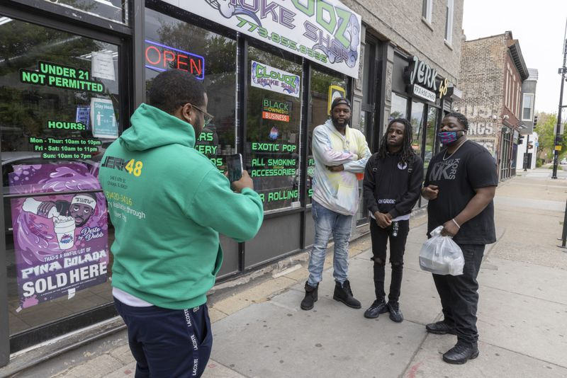 From left to right, Jerk 48 and Cloudz Smoke Shop co-owner Jarius Brunner takes a photo for a fan of Big 'Toine and social media influencer Korporate near Jerk 48, a restaurant used frequently for Korporate's skits at 548 E. 67th St. in West Woodlawn.