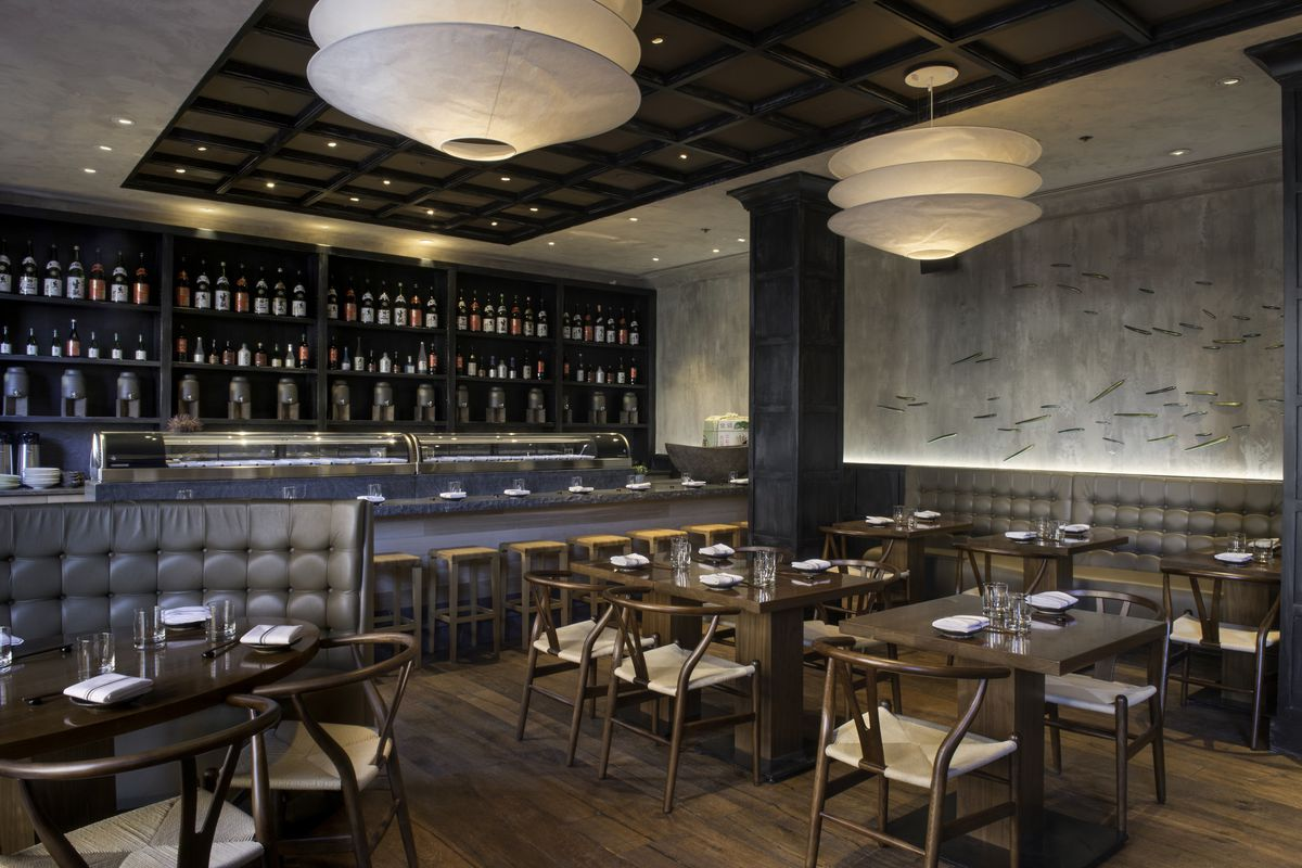 A classy restaurant interior with gray walls and booths, a hardwood floor, and striking round light fixtures