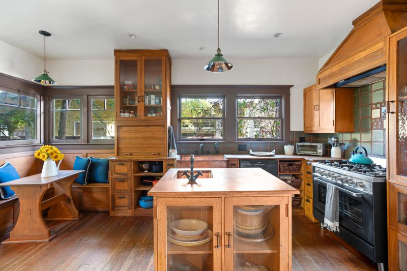 Kitchen with wooden island and built-in seating.