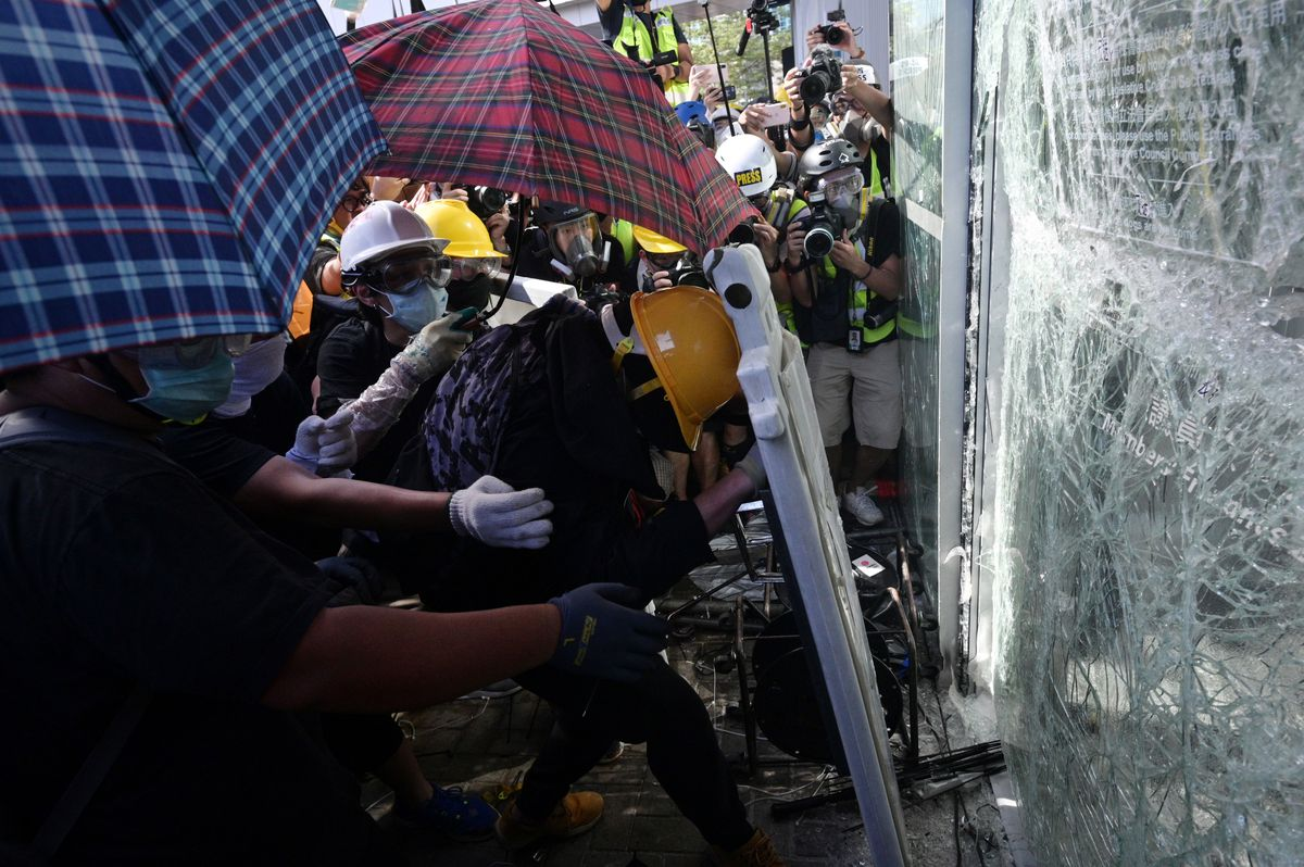 Protesters shatter glass windows as they try to get inside the legislative building on July 1, 2019.
