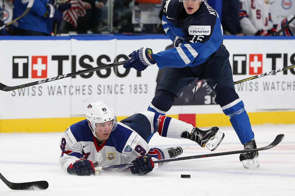 BUFFALO, NY - DECEMBER 31: Josh Norris #9 of United States tries to control the puck after being knocked to the ice by Joona Koppanen #15 of Finland in the first period during the IIHF World Junior Championship at KeyBank Center on December 31, 2017 in Bu