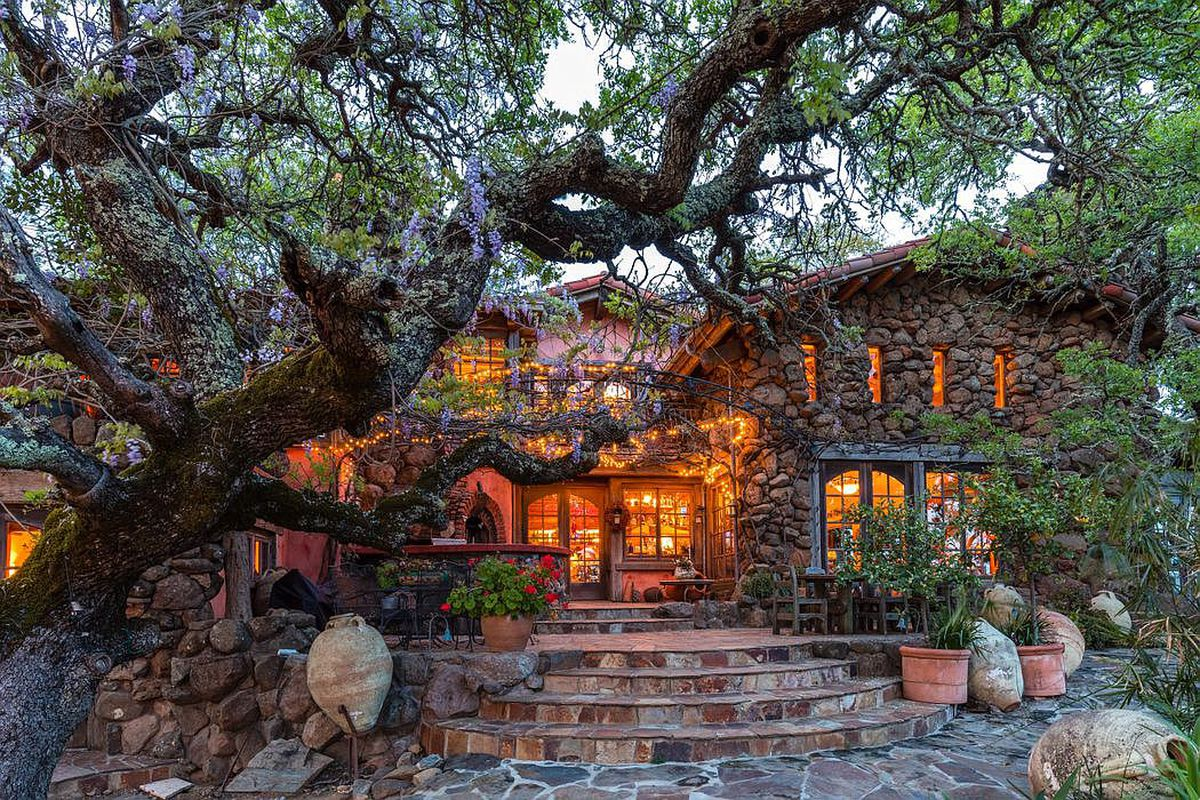A stone house in Napa Valley, surrounded by trees and vines.