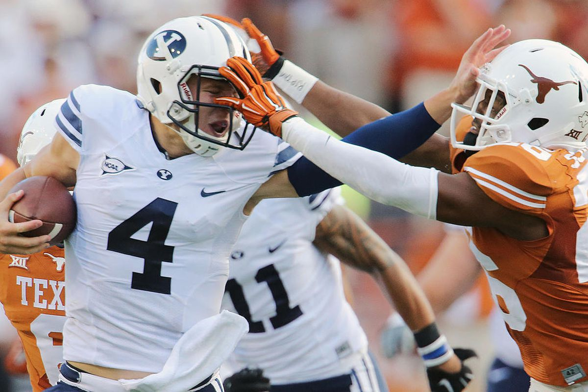 BYU's quarterback Taysom Hill pushes Texas' Adrian Colbert away on a run that was called back as BYU and Texas play Saturday, Sept. 6, 2014, in Austin Texas.