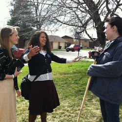 Sister Aubrey Allen, 20, of Portland, Ore., and Sister Ricelia Magana, 21, of Dallas, talk with Orem, Utah, resident Kira Amann, who was raking her yard on Thursday afternoon, April 3, 2014. Magana is a sister training leader in the Utah Provo Mission of the LDS Church and spent 24 hours with Allen on a companionship exchange, providing leadership and love.