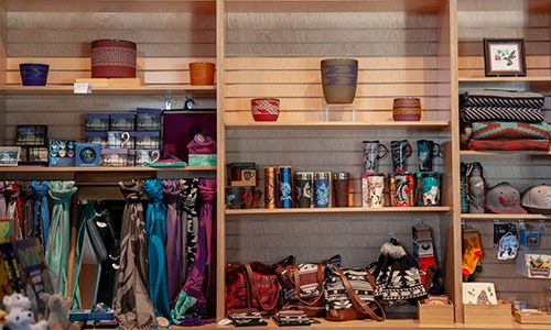Wooden shelves full of gift shop wares, including scarves, candles, and mugs.