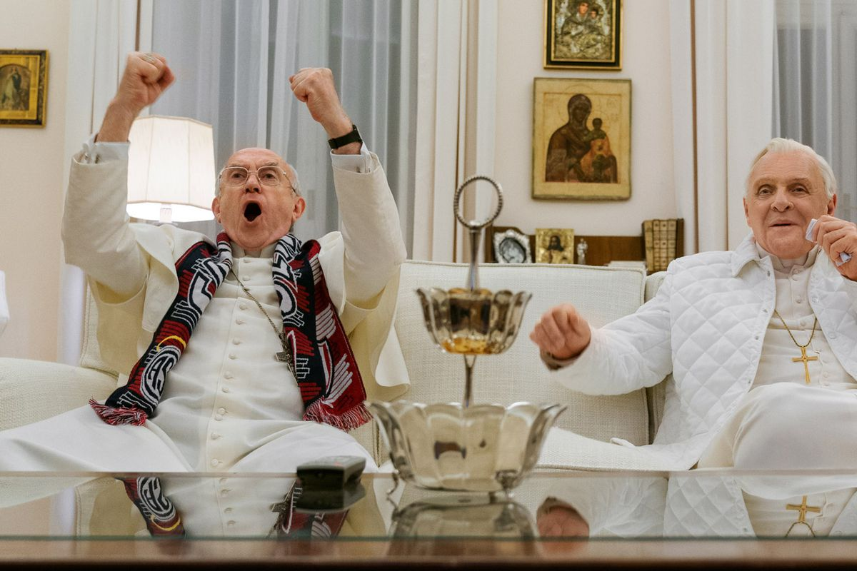 As Pope Francis, Jonathan Pryce cheers on his football team, while Anthony Hopkins, playing Pope Benedict XVI, watches.