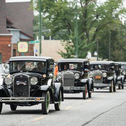 People drive vintage cars down South Cottage Grove Avenue during the Pullman National Monument's opening day in the Pullman neighborhood, Saturday morning, Sept. 4, 2021.