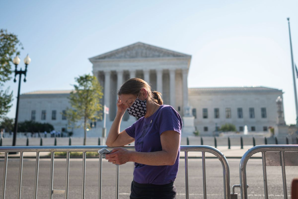 A woman watches a private ceremony on her cellphone for the late Supreme Court Justice Ruth Bader Ginsburg as she lies in repose, at the steps of the Supreme Court in Washington, DC, on September 23, 2020.