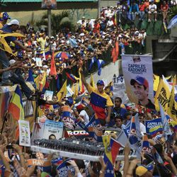 CORRECTS BYLINE - Opposition presidential candidate Henrique Capriles, center, gestures to supporters during a campaign rally in Caracas, Venezuela, Sunday, Sept. 30, 2012. Presidential elections in Venezuela are scheduled for Oct. 7.