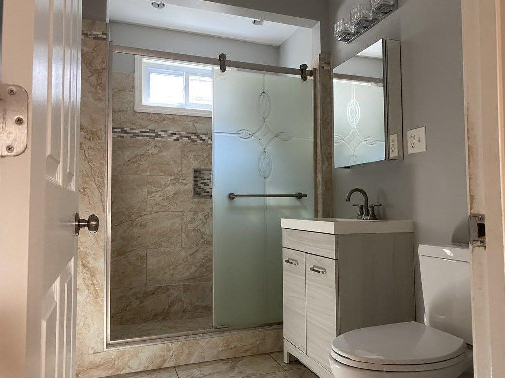 A bathroom with a toilet next to a vanity next to a shower with a sliding door.