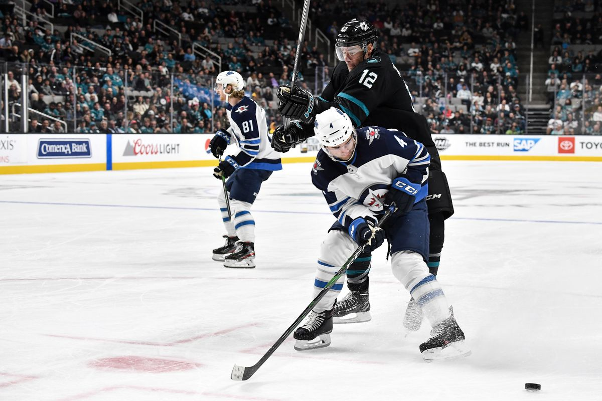 SAN JOSE, CA - NOVEMBER 1: Patrick Marleau #12 of the San Jose Sharks battles for the puck against Neal Pionk #4 of the Winnipeg Jets at SAP Center on November 1, 2019 in San Jose, California.