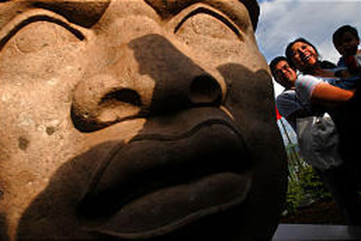 The Villareal family of Provo, Jared, left, his wife, Dely, and son, Jarzaih, gather around the Olmec head after its unveiling at the Utah Cultural Celebration Center in West Valley City. The head is a gift from Mexico.
