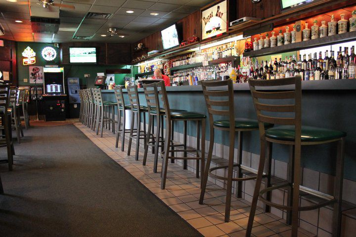 A line of stools before a green laminate bar. Behind the bar is a collection of booze bottles.