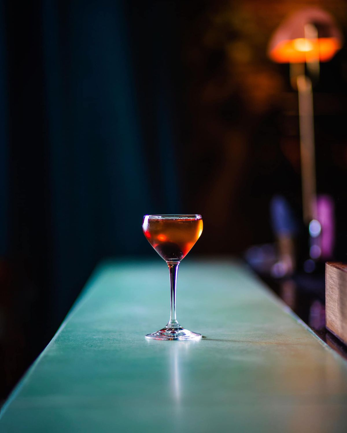 A whiskey cocktail sits on a green bar.
