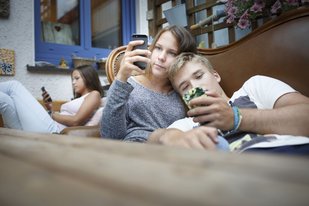 Three teens in a room, each looking at his or her phone