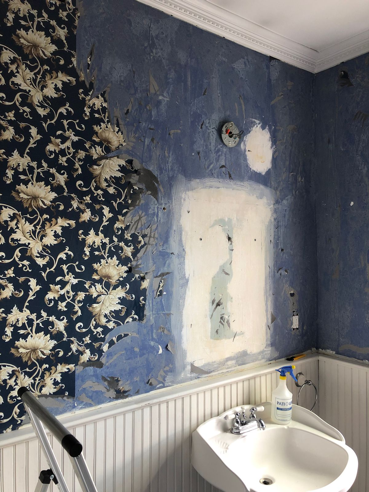 The original painted blue wall in the bathroom is on display while the dark patterned wallpaper is being removed.