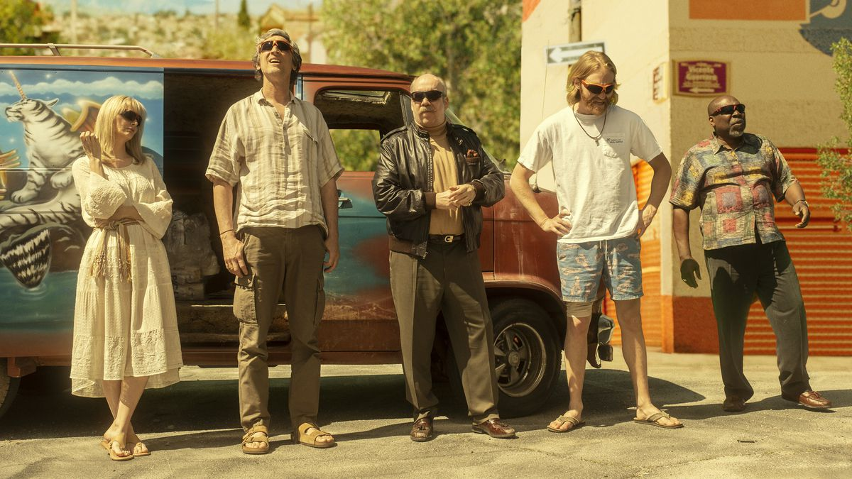 The Lodge 49 characters standing in a line outside a multicolored van.