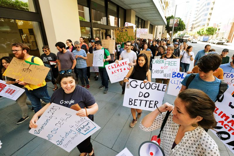 """Protesters for the Global Climate Strike hold signs that read, """"Google do better,"""" and, """"Climate action now."""""""