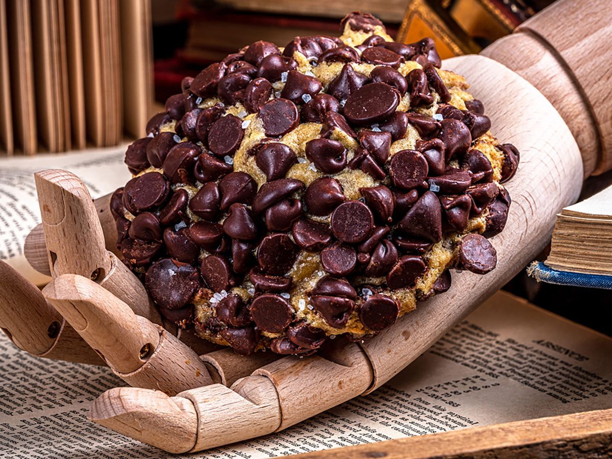 A wooden hand laying on an open book holding a cookie covered in chocolate chips