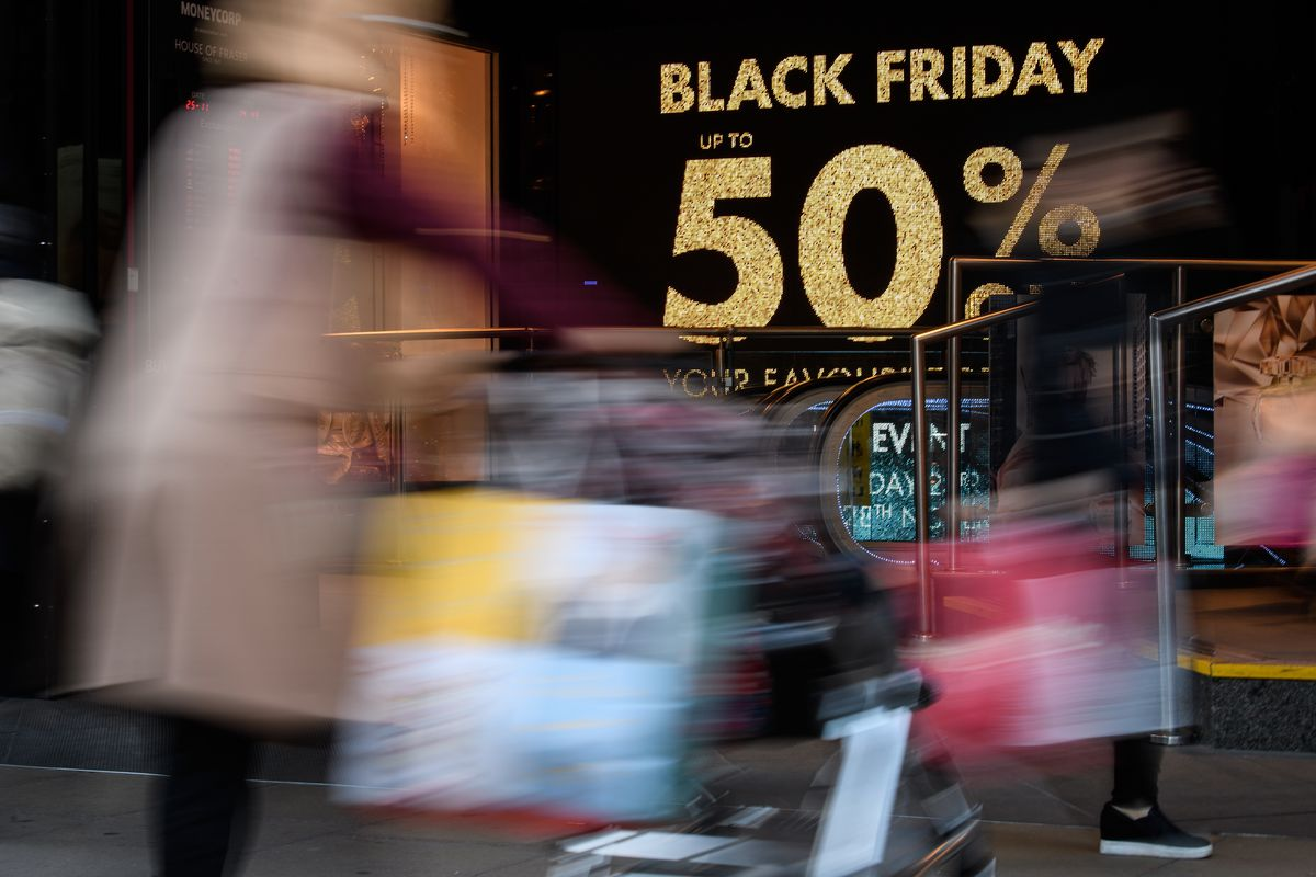 """Shoppers carry their purchases on Oxford Street as stores offer discounted items in their """"Black Friday"""" sales on November 25, 2016 in London, England"""