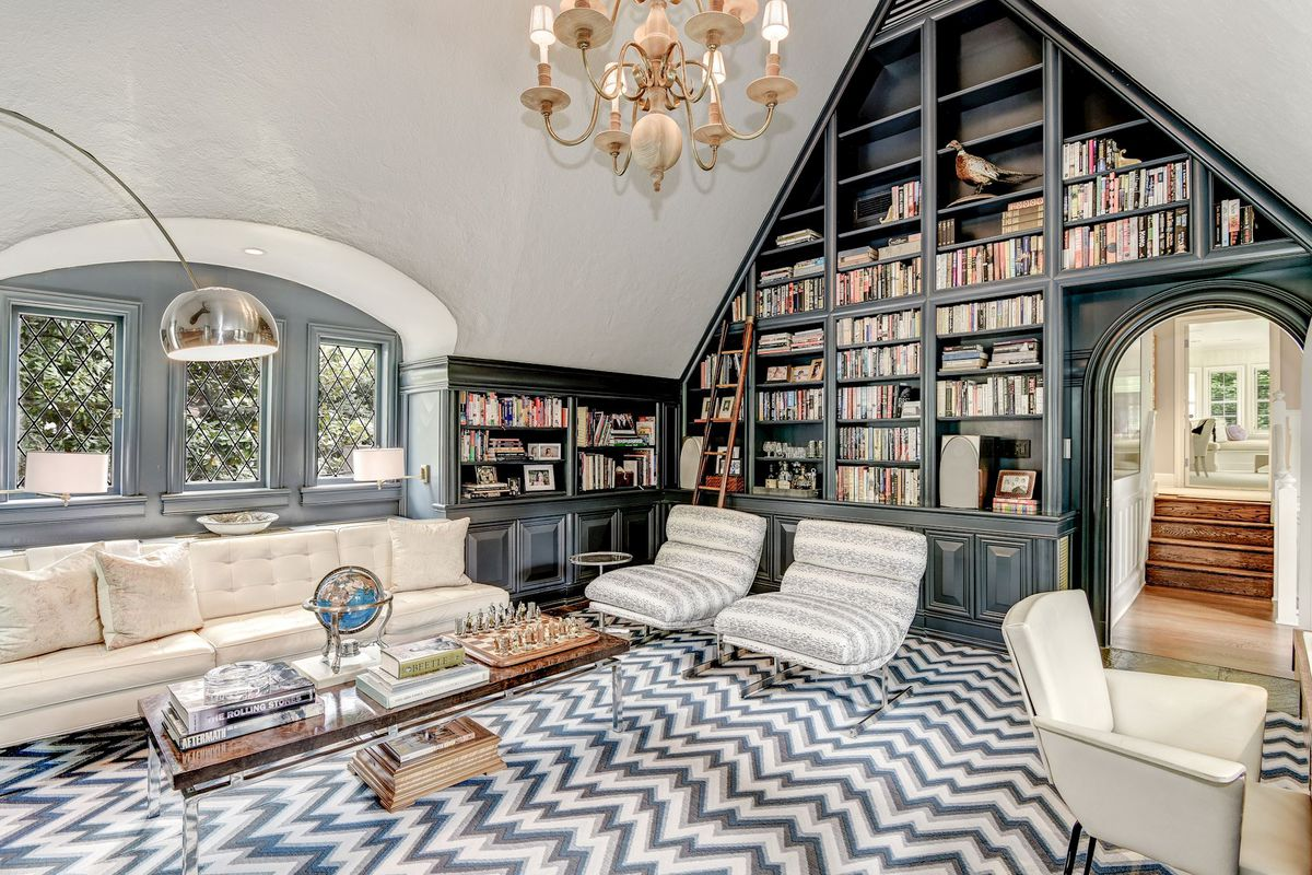 Vaulted ceilings in an upper bedroom with a chevron pattern carpet, gray built-in bookshelves, and seating.