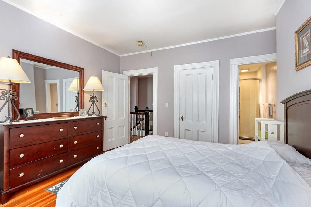A bedroom with a bed, a long dresser with a mirror above it, and a bathroom with the door open.