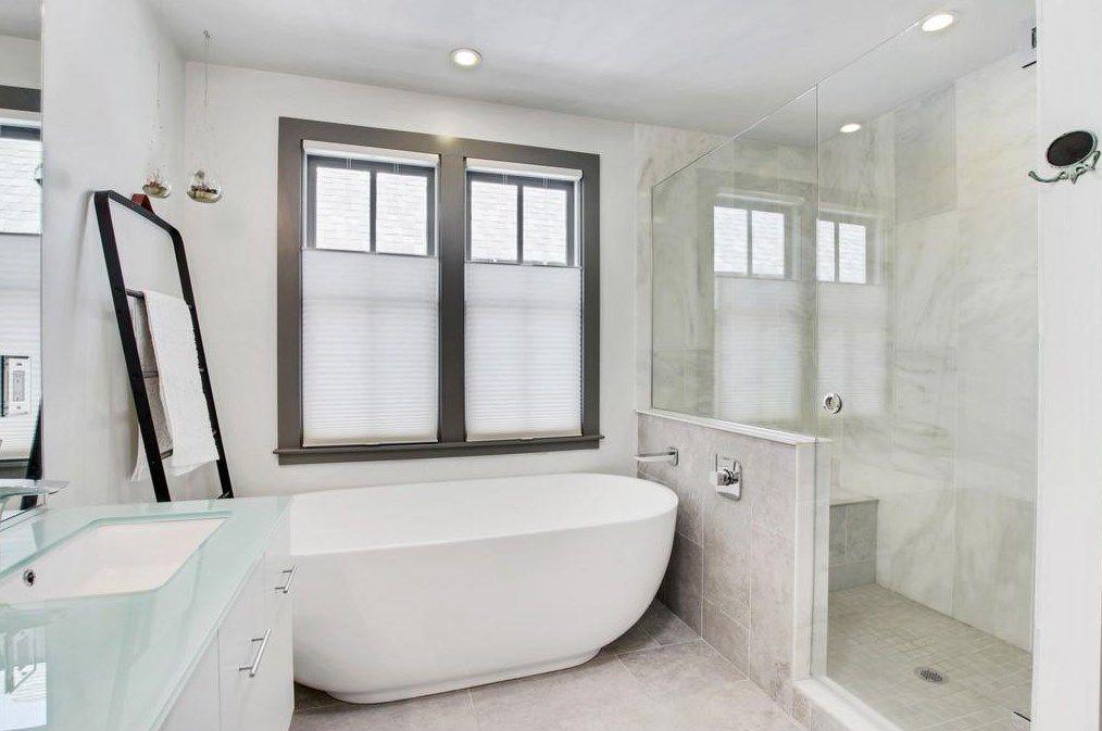 A big white master bathroom with a tub.