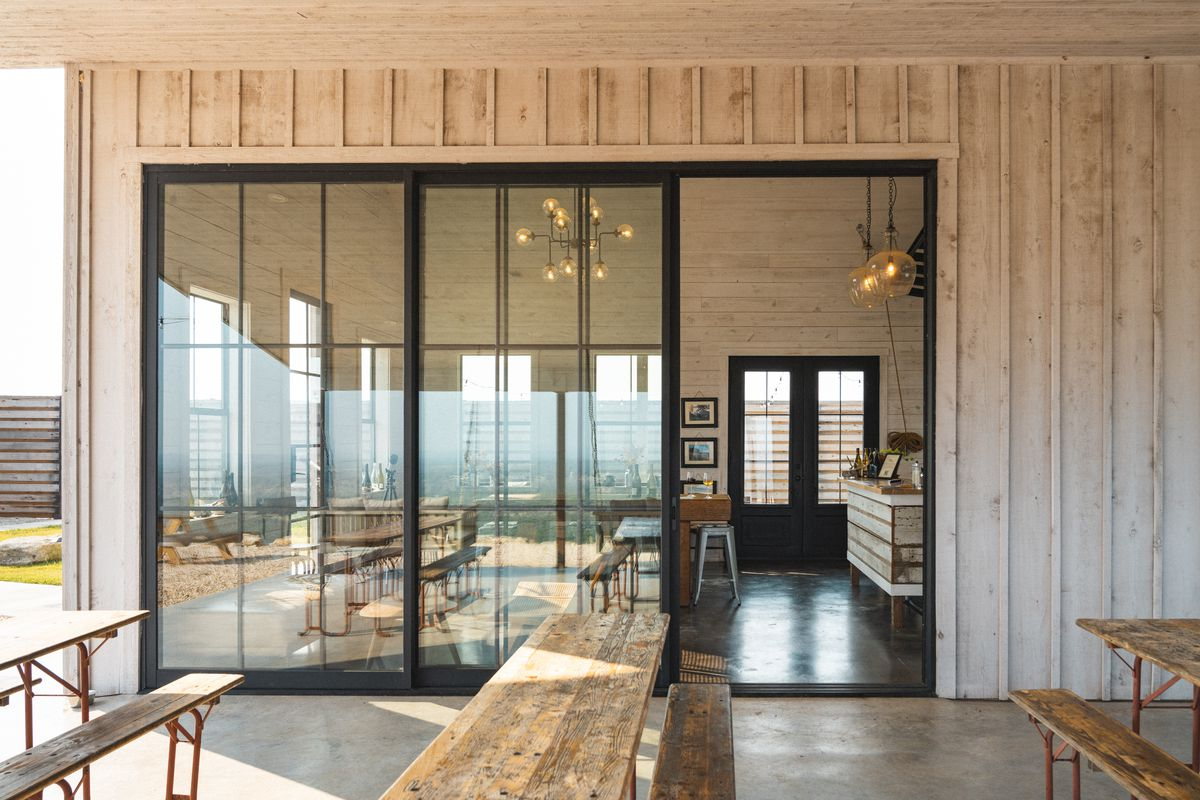 Picnic tables sit on a concrete patio in front of three-pane glass windows and a sliding door opened to a room with tables and lights on.