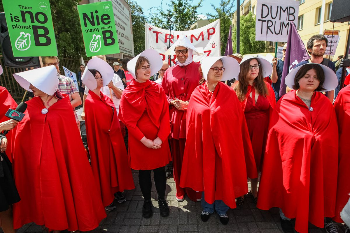 """People dressed as characters from """"The Handmaid's Tale"""" and people holding anti-Trump posters and banners"""