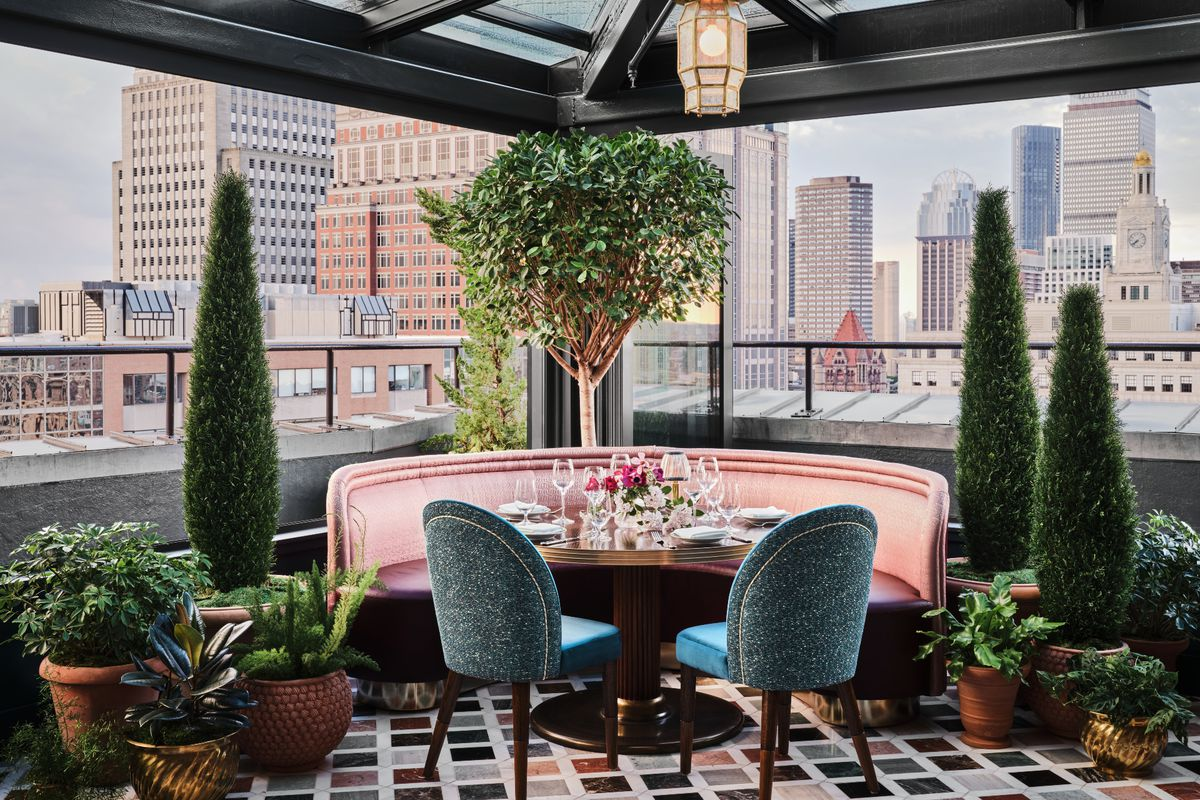 A round restaurant table features rose-colored booth seating and teal chairs. The floor is marble with a multi-colored diamond pattern, and the table is surrounded by plants. Views of Boston's Back Bay are clearly visible behind the table.