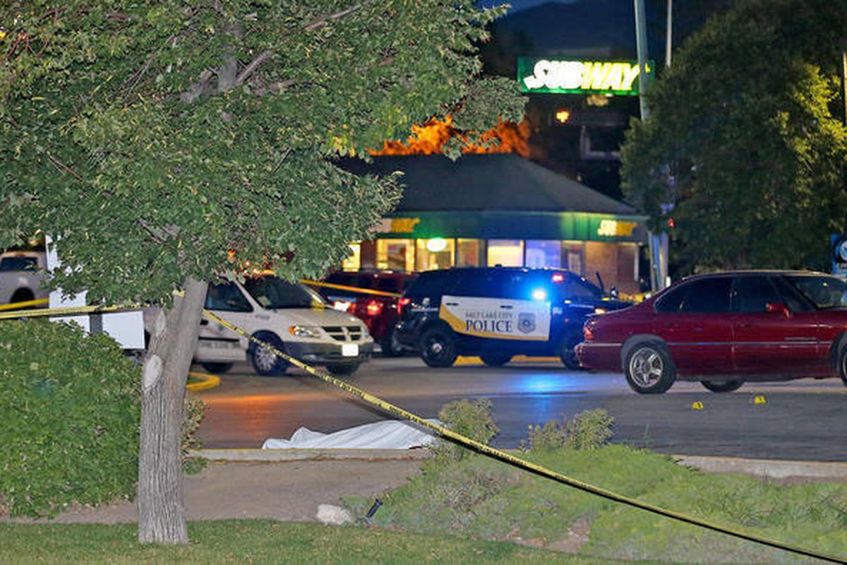 The body of a man who was shot in the parking lot of a 7-Eleven store at 2102 S. State is covered on Monday, Aug. 11, 2014, in South Salt Lake.