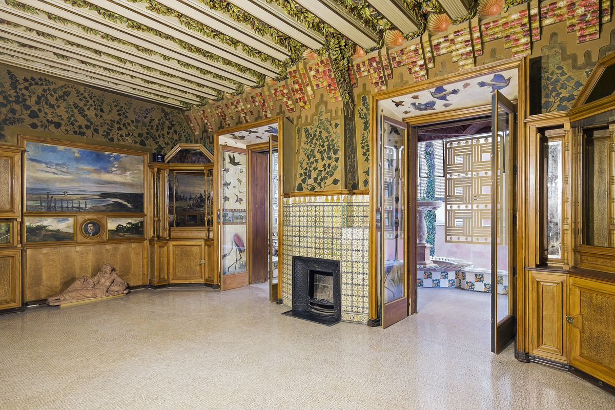 Interior shot of ornate great room with two door open to a patio, small fireplace, tiled and otherwise decorated walls, terrazzo floors, and artwork.