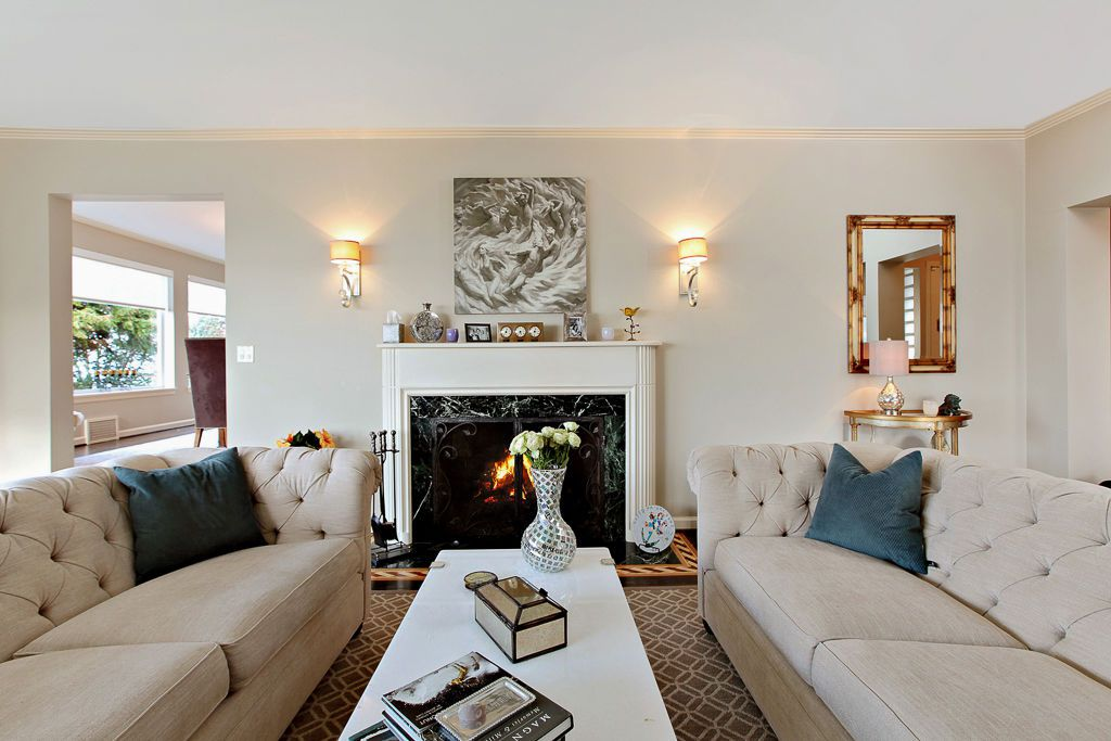Two tan couches on either side of a black marble fireplace