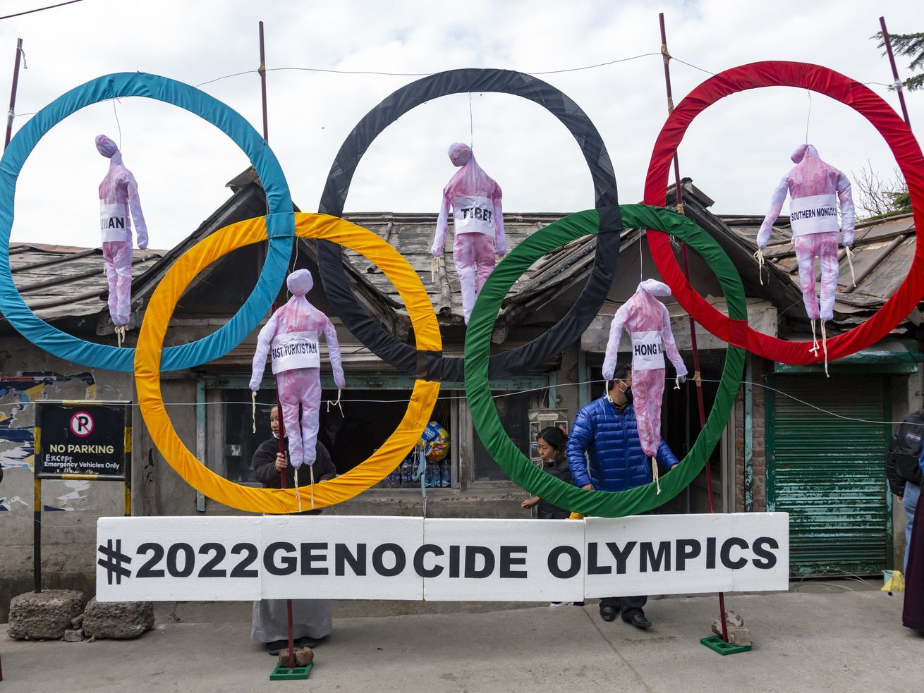 In this Feb. 3, 2021, file photo, exile Tibetans use the Olympic Rings as a prop as they hold a street protest against the holding of the 2022 Beijing Winter Olympics, in Dharmsala, India.