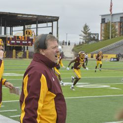 CMU head coach Jim McElwain reacts to a kickoff scrum happening in front of the sideline.