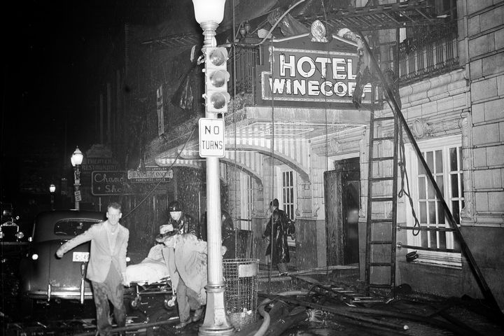 The exterior of the Winecoff Hotel. There is a person on a stretcher. The stretcher is being carried by a few men. The hotel has just had a fire and there is damage to the exterior.
