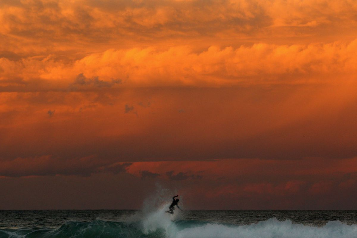 A surfer jumps off a wave at sunset at Bronte Beach on April 24, 2012 in Sydney, Australia.