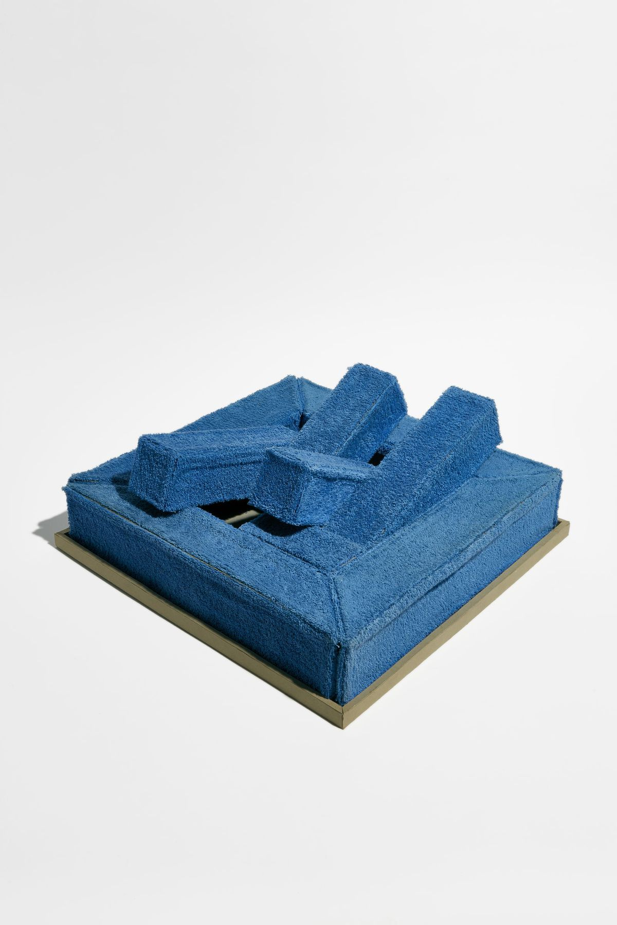 A square blue sofa with large blue cushions.