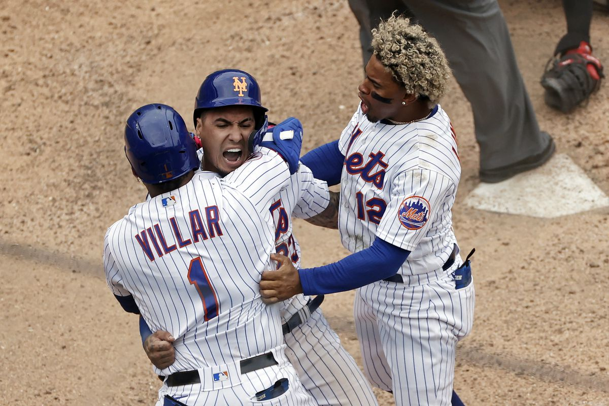 The Mets' Javier Baez celebrates with Jonathan Villar and Francisco Lindor, right, after scoring the game winning run against the Miami Marlins on Tuesday.
