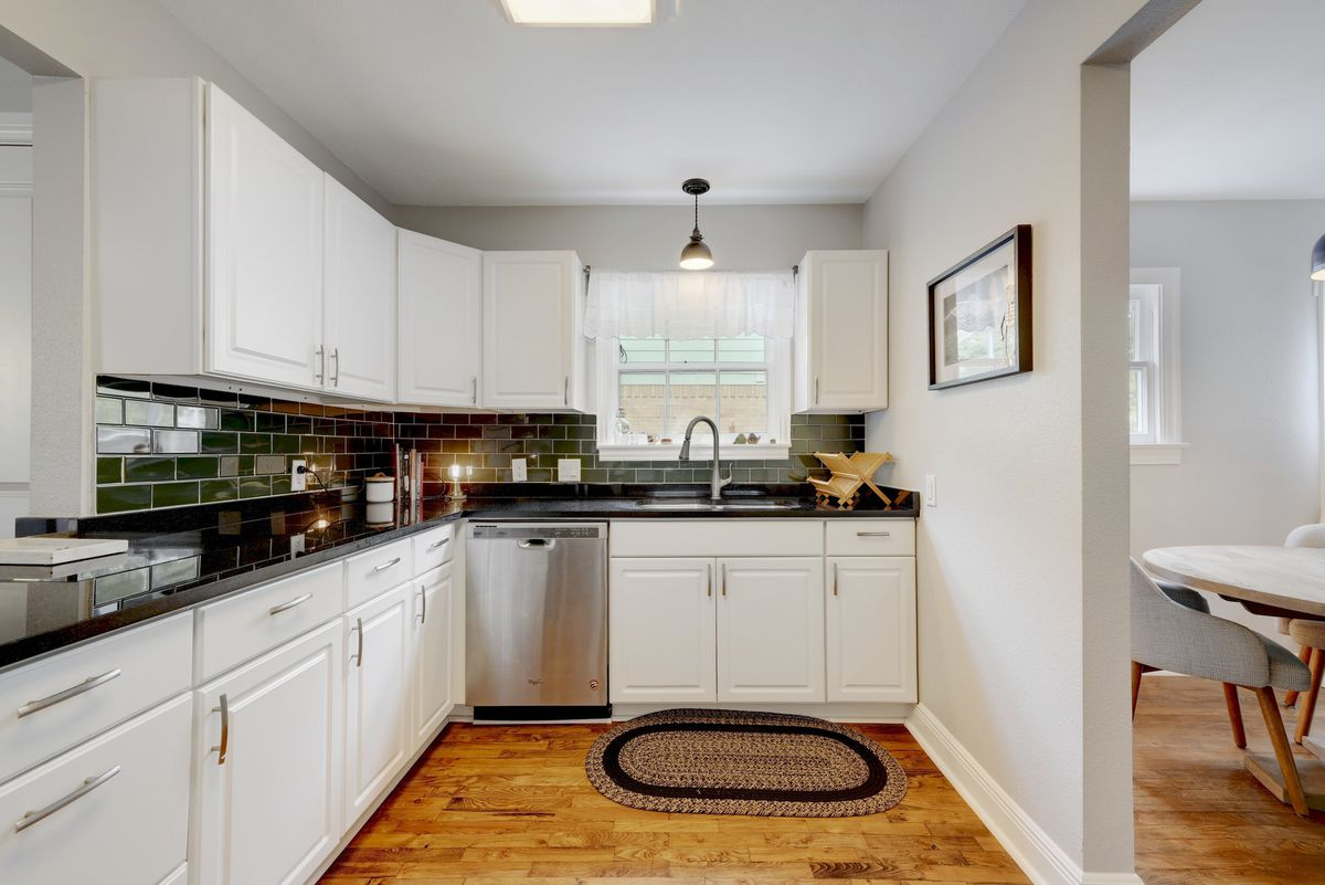 A small kitchen with white cabinetry and a forest green subway tile backsplash. This view is looking towards the sink which is under the kitchen window.