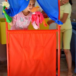 Two Syrian girls play with puppets in the kindergarten at the Kyllini refugee camp in Myrsini, Greece, July 11, 2016. The camp was previously a luxury resort before it fell into disrepair and was later turned into a refugee camp.