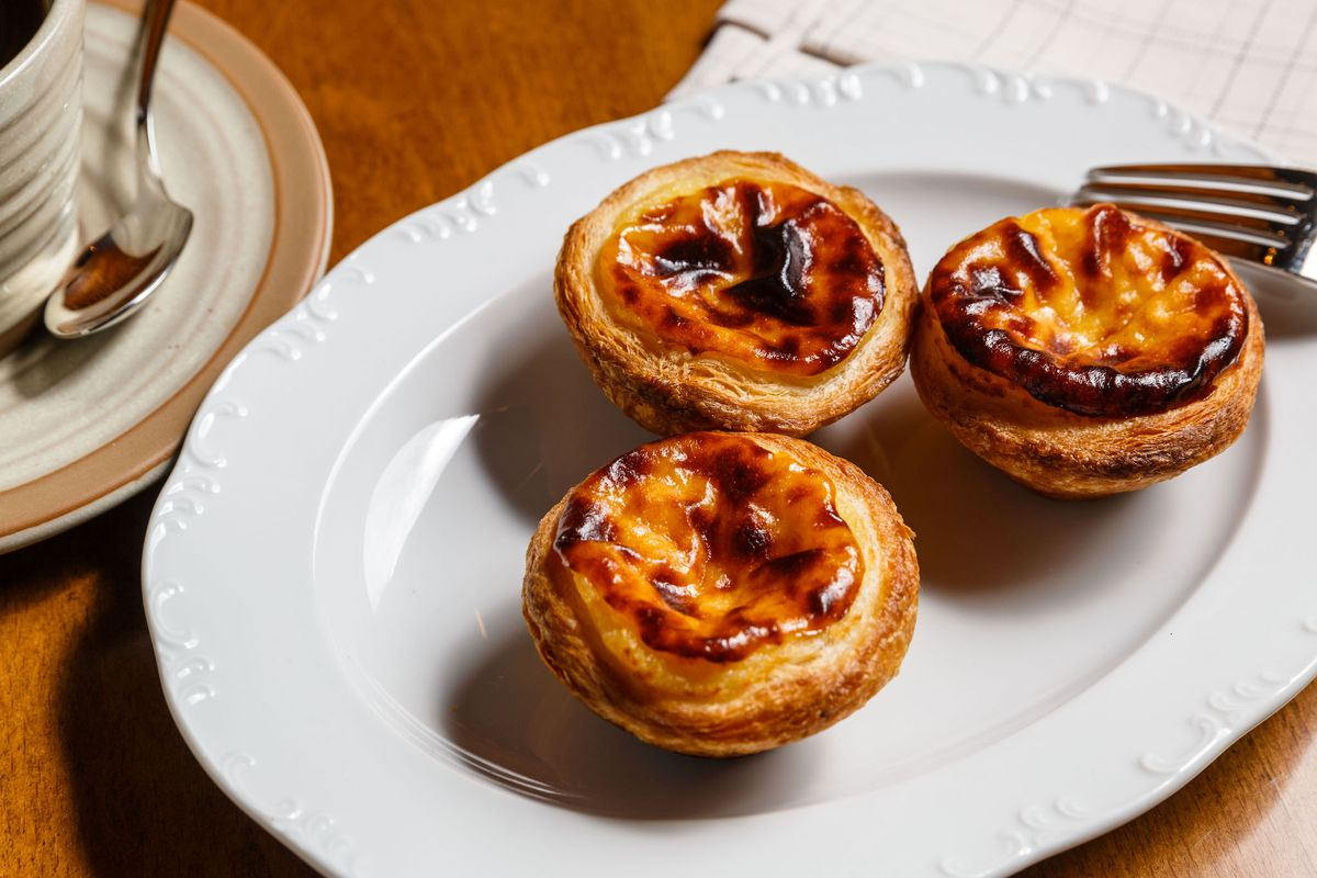 A white plate of three yellow and burnt top pastries with a fork to the side on a wood table.
