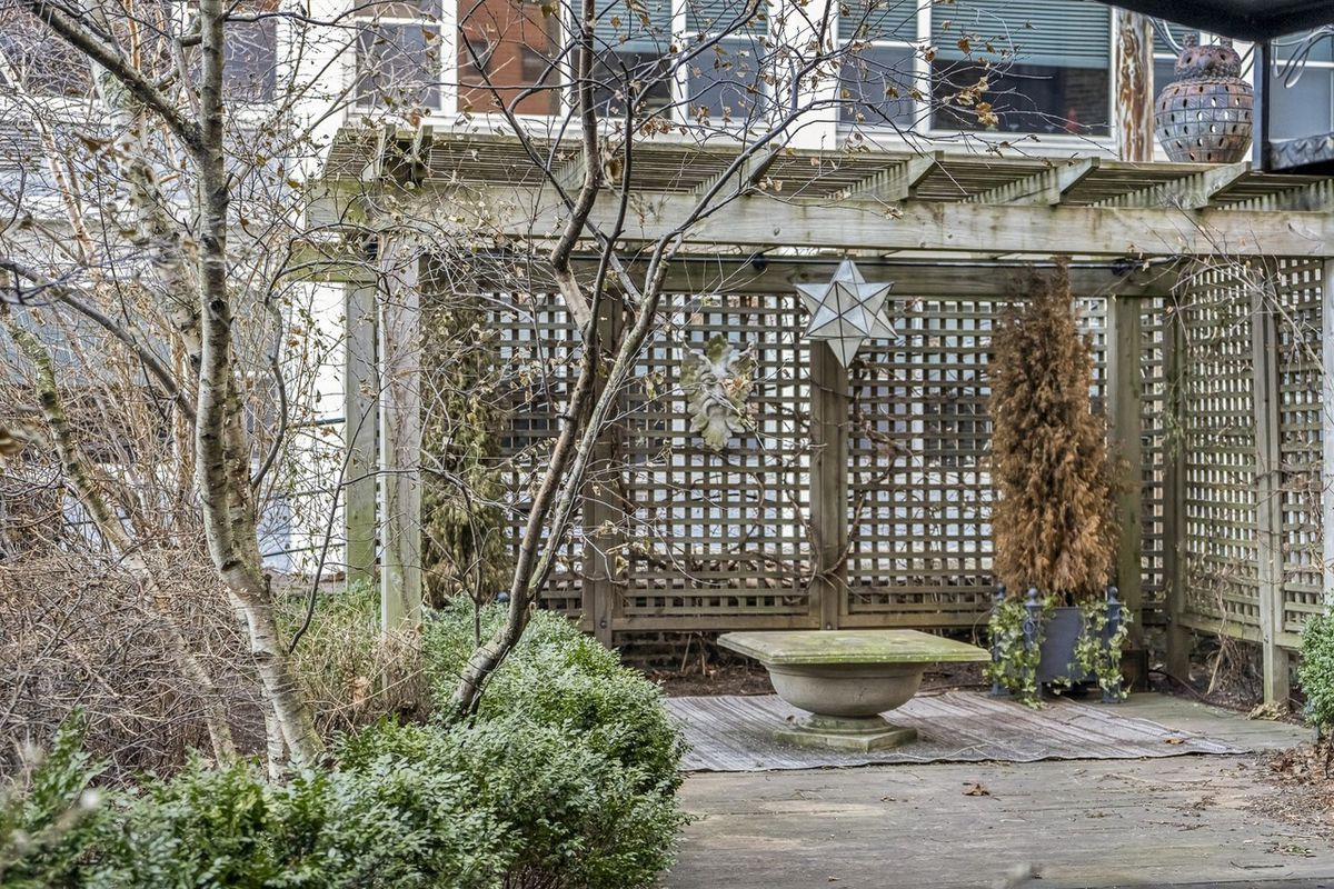 A view of the back patio with landscaping and potted plants.