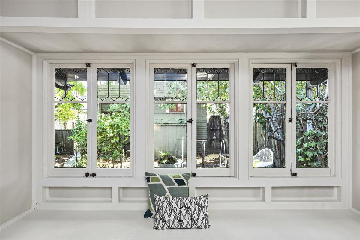 Three pairs of windows, side by side, highlight a white nook. You can see trees and the building next door from these windows.